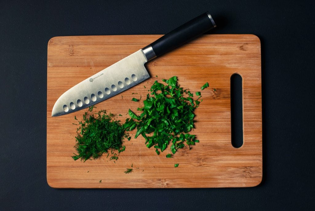 santoku knife with herbs on a cutting board.