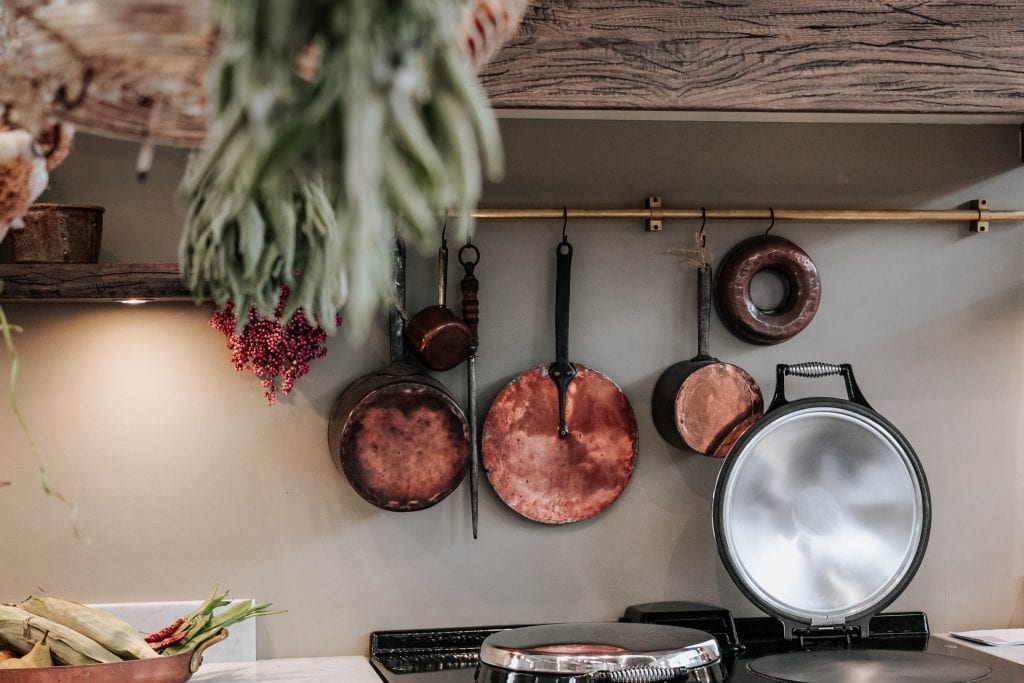 Copper pans hang on a kitchen wall.