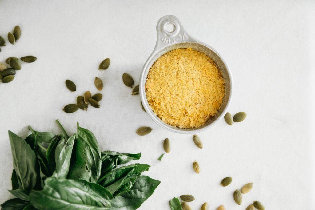 Nutritional yeast in a 1/3 cup measuring utensil, alongside other ingredients for vegan basil pesto.