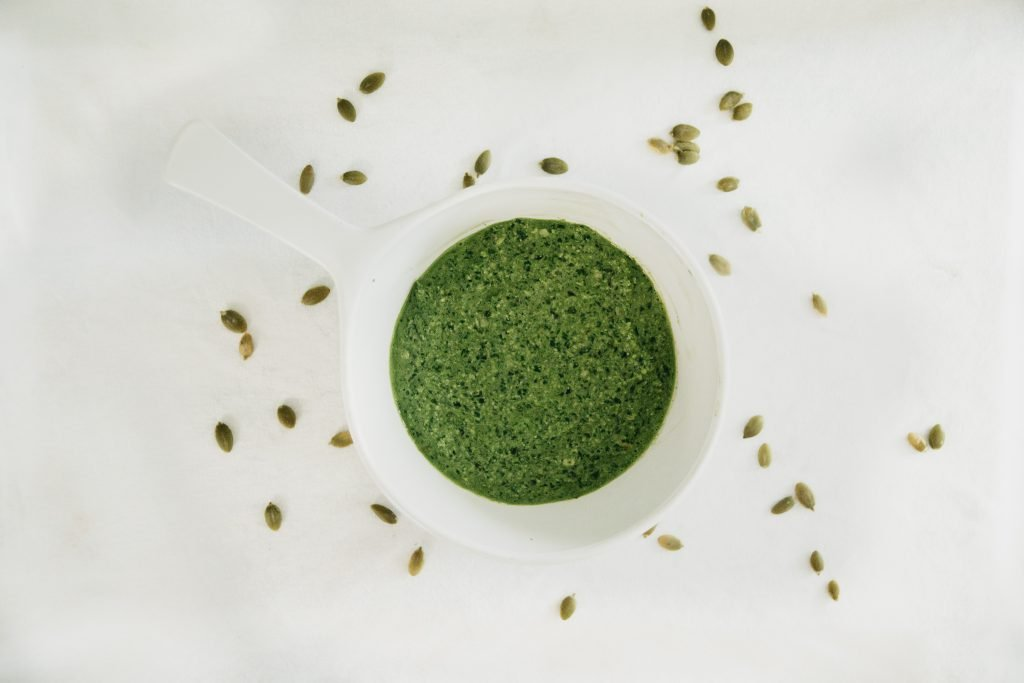 Vegan pesto in a dish, surrounded by pumpkin seeds, as seen from above.