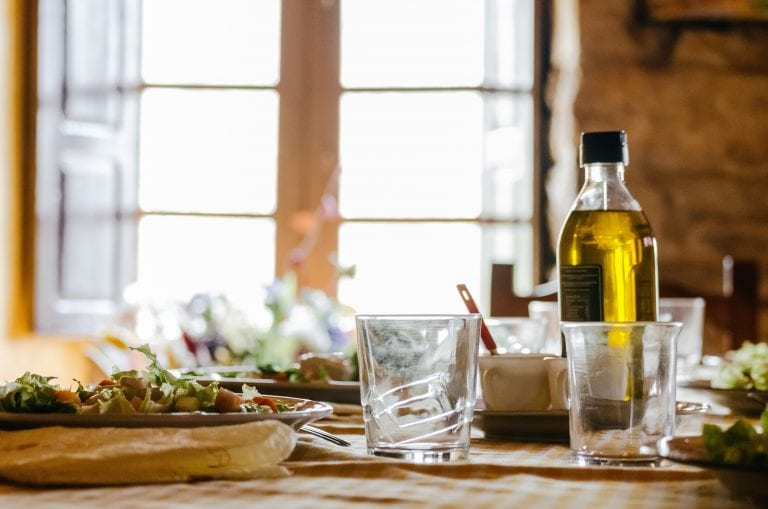 Olive oil bottle on a busy kitchen counter.