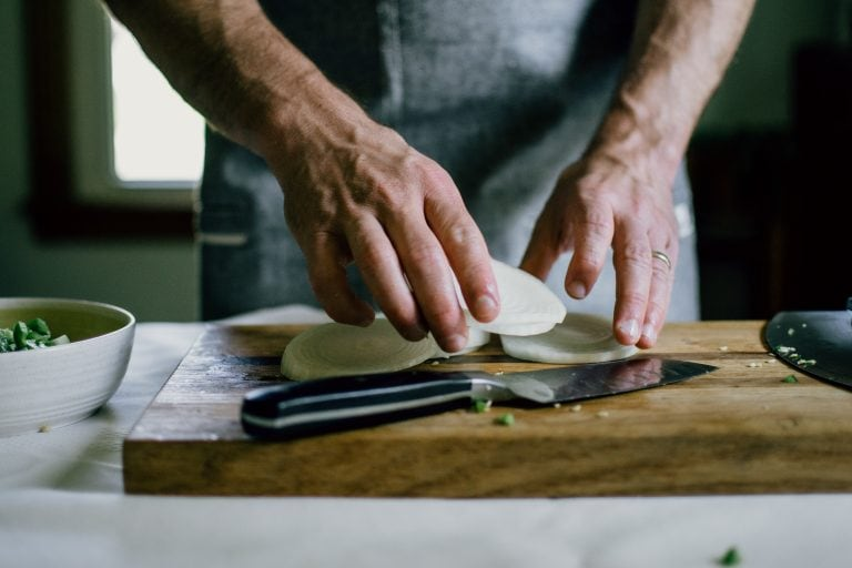 Kitchen Ambition founder David Lewis slicing an onion.