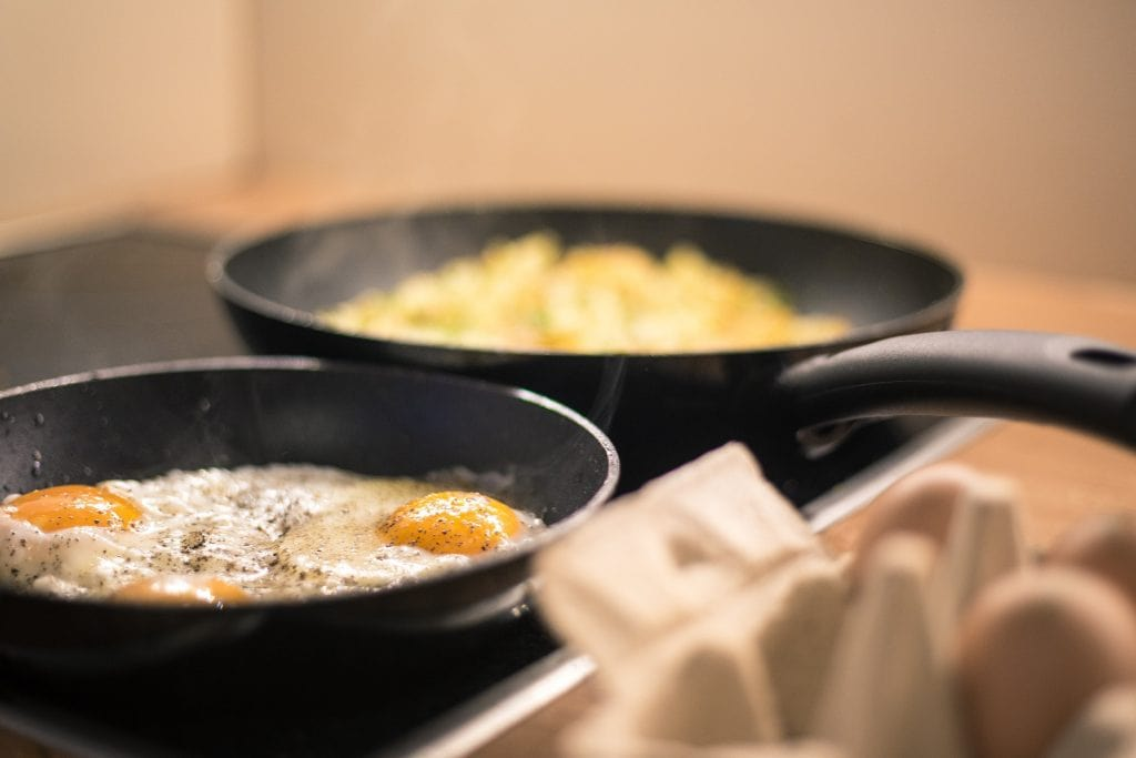Eggs frying in two non-stick pans.